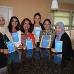 Group of women posing with Daisy Khan and the WISE UP: Knowledge Ends Extremism booklets