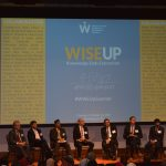 Eight people seated on the WISE Summit stage with the WISE UP logo behind them